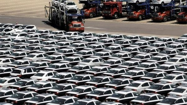 File Photo: A carrier trailer transports newly manufactured cars at a port in Dalian, Liaoning province, China.