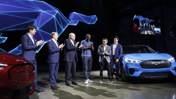 Bill Ford, chairman of Ford Motor Co., from second left, Jim Hackett, president and chief executive officer, actor Idris Elba, and Hau Thai-Tang, chief product development and purchasing officer, applaud during a reveal event for the Mustang Mach-E electric sports utility vehicle (SUV). (Bloomberg)