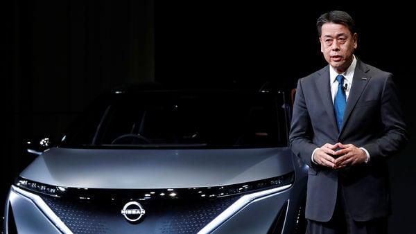Nissan Motor's chief executive Makoto Uchida next to the Ariya Concept car. (REUTERS)