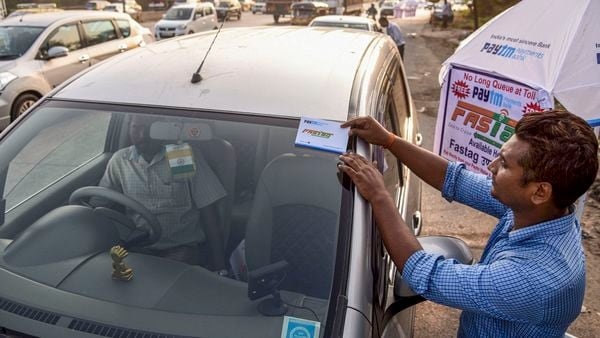 File photo: A worker fixes a FASTag sticker on the windscreen of a car. (PTI)