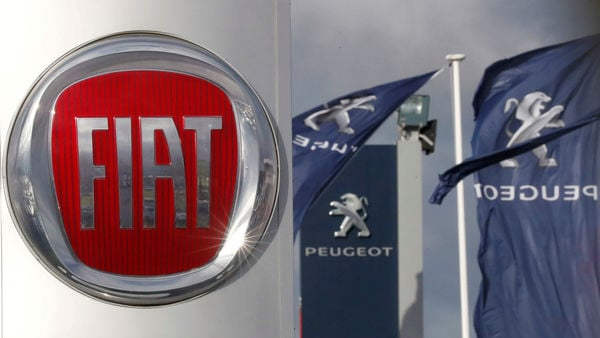 FILE PHOTO: The logos of car manufacturers Fiat and Peugeot are seen in front of dealerships of the companies in Saint-Nazaire, France, November 8, 2019. REUTERS/Stephane Mahe
