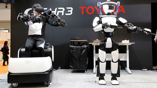 Toyota Motor Corp.'s human-shaped T-HR3 robot, right, is remotely controlled by its staff member, left, during a demonstration in Tokyo. (AP)