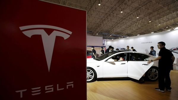 FILE PHOTO: People view a Tesla car during the Auto China 2016 in Beijing, China, April 25, 2016. REUTERS/Jason Lee