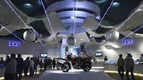 Visitors walk at TVS motorcycle pavilion at an auto expo in New Delhi January 6, 2010. REUTERS/Adnan Abidi/Files
