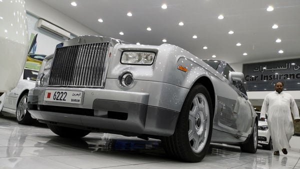 FILE PHOTO: A customer walks next to a Rolls Royce for sale at a second hand car showroom Classic Motors Showroom in Sanabis, west of Manama, Bahrain, April 11, 2019. Picture taken April 11, 2019. REUTERS/Hamad I Mohammed