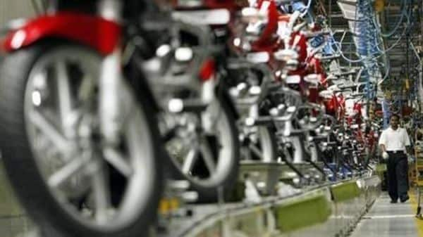File Photo: A worker walks beside newly built motorbikes at the Bajaj Auto Ltd. plant in Pune, about 130 km (82 miles) from Mumbai August 9, 2007. REUTERS/Punit Paranjpe/Files
