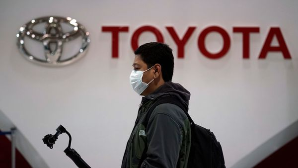 FILE PHOTO: A visitor walks by the logo of Toyota at its showroom Thursday, Jan. 30, 2020, in Tokyo. German automaker Volkswagen has kept its lead as the world's largest automaker as Japanese rival Toyota sold fewer vehicles last year. Toyota Motor Corp. said Thursday it sold 10.74 million vehicles around the world in 2019, trailing Volkswagen at 10.97 million vehicles. (AP Photo/Eugene Hoshiko) (AP)