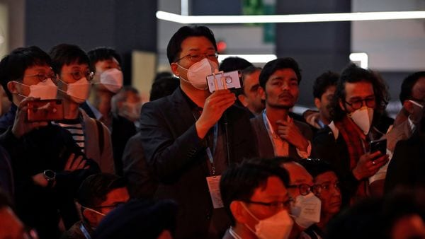 Visitors use their mobile phones to film vehicles at the India Auto Expo 2020. (REUTERS)