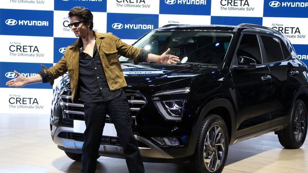 Bollywood actor Shahrukh Khan performs his signature step during the launch of Hyundai's all-new Creta at Auto Expo 2020.