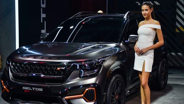 Greater Noida: A model poses next to a Kia Seltos car displayed at the Auto Expo 2020 in Greater Noida, Wednesday, Feb. 5, 2020. (PTI Photo/Ravi Choudhary) (PTI2_5_2020_000177A) (PTI)