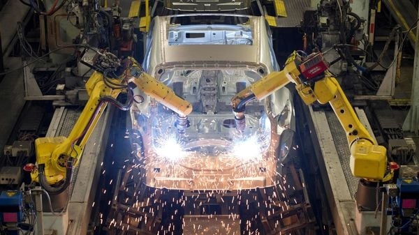 (FILES) In this file photo taken on November 12, 2014 Robots weld vehicle panels in the Body Shop at the Nissan Sunderland Plant in North East England. (Photo by Oli SCARFF / AFP) (AFP)