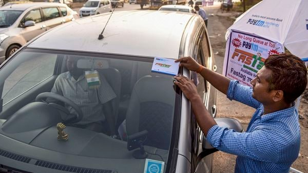 Navi Mumbai: A worker fixes a FASTag sticker on the windscreen of a car, at Vashi Toll Plaza on Sion Panvel Highway, Mumbai, Friday, Nov. 29, 2019. From Dec. 1, making toll payments via FASTag will become mandatory at national as well as state highways. (PTI Photo) (PTI)