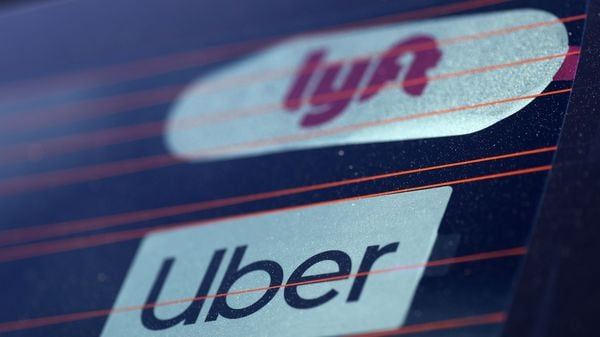 FILE PHOTO: Uber and Lyft signs are seen on a car in Redondo Beach, California, U.S., March 25, 2019. REUTERS/Lucy Nicholson