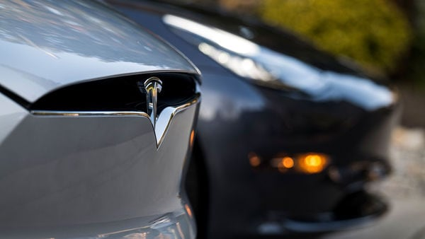 A Tesla badge is displayed on a Model X electric vehicle in San Ramon, California. Tesla Chief Executive Officer Elon Musk is pushing the Solar Roof and batteries as essential components of the company's drive to reduce fossil fuel use. Photographer: David Paul Morris/Bloomberg (Bloomberg)