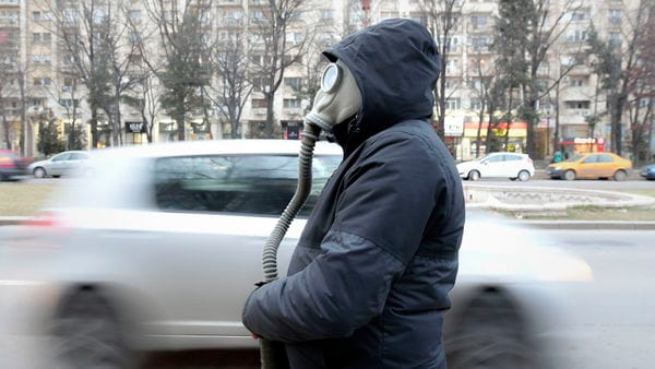 Cars drive by a man wearing a vintage gas mask during a climate and anti-pollution protest in Bucharest, Romania. (AP)