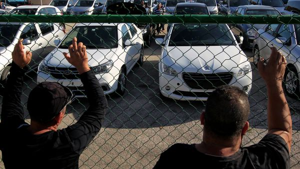 People gather outside a government lot where used cars are for sale, in Havana, Cuba. (REUTERS)