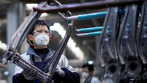 An employee wearing a face mask works on a car seat assembly line at Yanfeng Adient factory in Shanghai, China, as the country is hit by an outbreak of a novel coronavirus, (REUTERS)