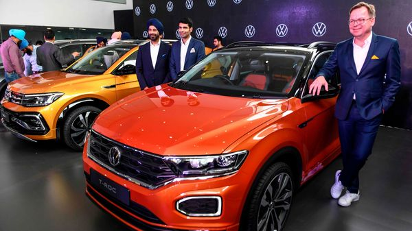 Volkswagen Passenger Cars' India Director, Steffen Knapp (R), gestures as he poses for photographs next to the T-Roc car during the unveiling event of three new SUVW(Sport Utility VolksWagen) models, Tiguan Allspace, T-Roc and Taigun, to customers in Amritsar on February 28, 2020. (AFP)