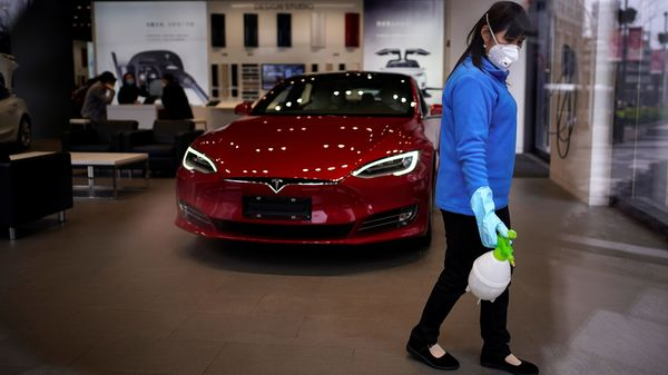 A worker sanitises a Tesla showroom, in a Shanghai shopping complex, as the country is hit by an outbreak of the novel coronavirus, Shanghai, China. (REUTERS)
