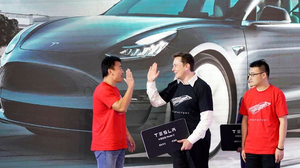 File photo of Tesla CEO Elon Musk posing with Tesla China-made Model 3 vehicle owners onstage during a delivery event at its Shanghai factory in China on January 7, 2020. (REUTERS)