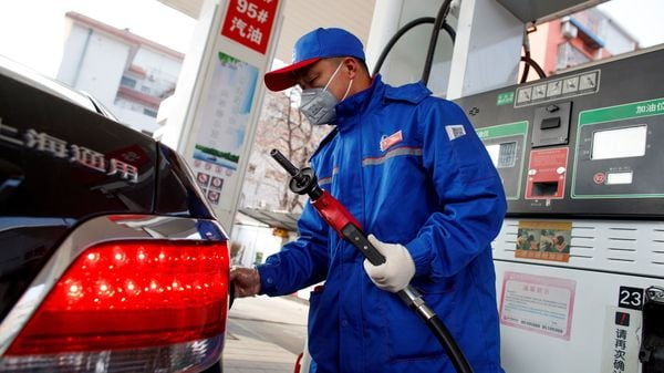 FILE PHOTO: A pump attendant wears a mask as he refuels a car at a Sinopec gas station where customers can buy supplies as the country is hit by an outbreak of the novel coronavirus, in Beijing, China, February 28, 2020. REUTERS/Thomas Peter/File Photo (REUTERS)