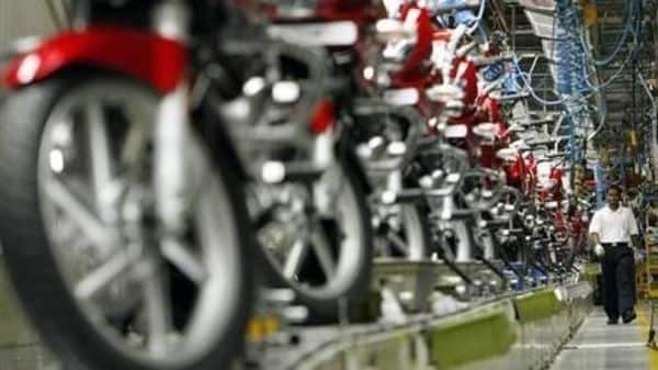 File photo - A worker walks beside newly built motorbikes at the Bajaj Auto Ltd. plant in Pune.