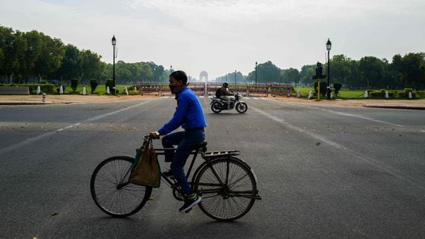 Commuters ride on a deserted Rajpath leading to India Gate during a government-imposed lockdown as a preventive measure against the COVID-19 in New Delhi on March 24, 2020. (AFP)