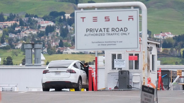 An employee of a Tesla Inc's US vehicle factory is seen at a security gate in Fremont, California. (REUTERS)