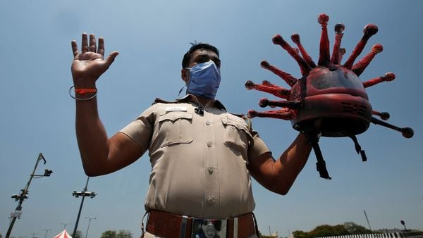 A police officer, shows a helmet depicting coronavirus, as he requests commuters to stay at home during a 21-day nationwide lockdown in Chennai. (REUTERS)