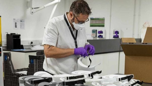 A JLR employee working on the 3D-printed protective visors