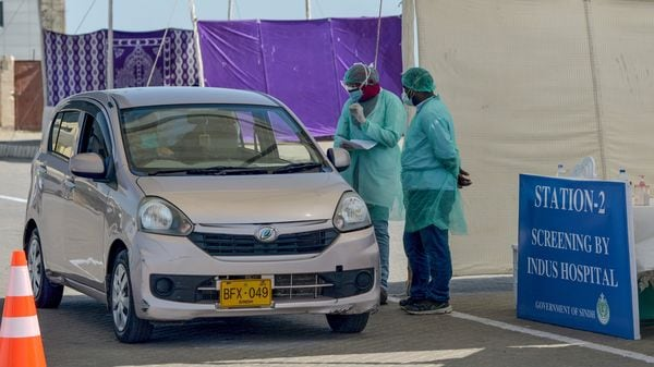 Medical staff members wearing protective gear take information from a resident sitting in a car for a coronavirus test at a drive-through screening and testing facility point in Karachi. (AFP)