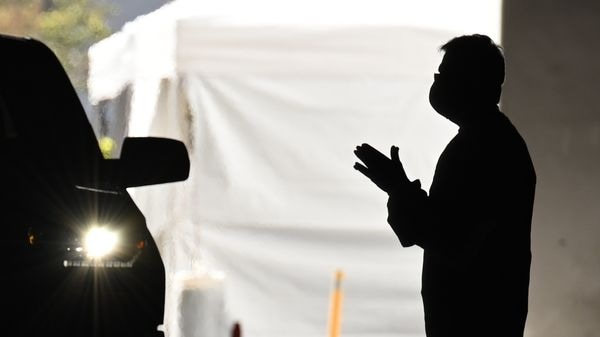 A health care worker instructs people arriving in their cars to be tested for COVID-19 in California. (AFP)