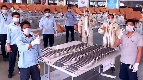 Workers at a Ford India plant with face shields being manufactured here.