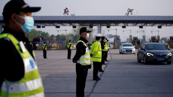 Police officers stand guard at a toll station of an expressway after travel restrictions to leave Wuhan, the capital of Hubei province and China's epicentre of the novel coronavirus disease (COVID-19) outbreak, were lifted. (REUTERS)