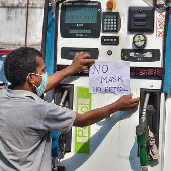 File photo: A worker pastes a notice that reads 'NO MASK NO PETROL' at a petrol pump after authorities made it mandatory for the people to wear mask while stepping out of their homes, during ongoing Covid-19 lockdown, in Kolkata, (PTI)