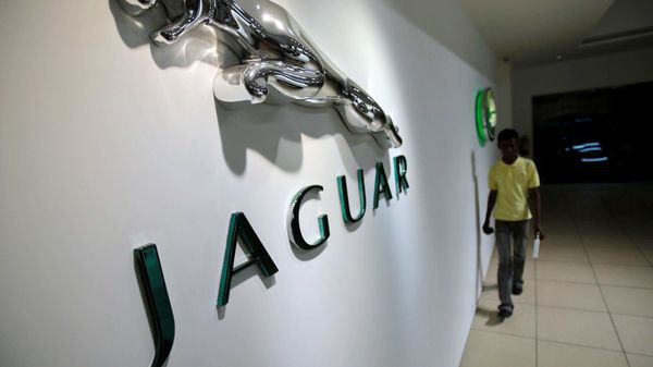 File photo: A showroom attendant walks past company logos at a Jaguar Land Rover showroom in Mumbai. (REUTERS)