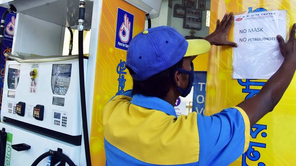 File photo: A worker put a poster `no mask no petrol` at a petrol pump as the area declared `hot spot` zone during coronavirus lockdown, in Kolkata.
