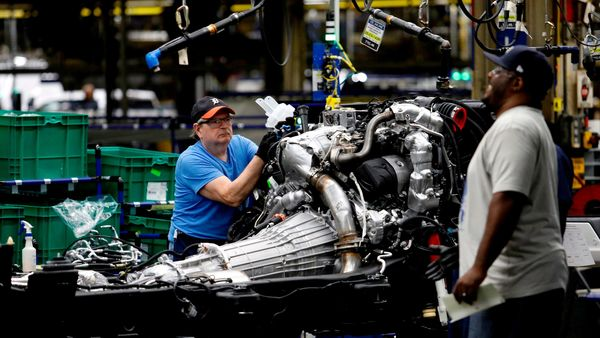 GM workers work on the chassis of full-size pickup trucks at the Flint Assembly plant in Michigan. (File photo) (AFP)