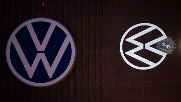 A cartoon of a Volkswagen logo squashing the coronavirus is displayed on a building at Volkswagen's headquarters to celebrate the plant's re-opening during the spread of the coronavirus disease. (REUTERS)