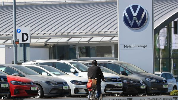 A cyclist passes used Volkswagen AG automobiles on the forecourt of a car showroom in Wolfsburg, Germany. (Bloomberg)
