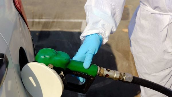 An employee wearing personal protective equipment (PPE) refuels a vehicle at a fuel station in New Delhi. (Bloomberg)