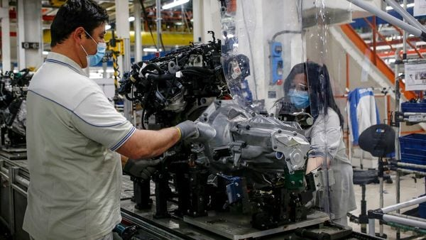 File photo: A plastic sheet is laid between two workers needing to face each other to perform their task, as a safety measure for coronavirus contamination, at the Fiat Chrysler Automobiles plants of Atessa, in Central Italy, (AP)