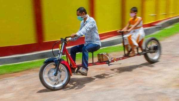 Self-made automobile engineer Partha Saha (L) tries his modified bike designed for social distancing as a preventive measure against the spread of the coronavirus, with his daughter Pragya Saha in front of their house in Aralia village on the outskirts of Agartala. (AFP)
