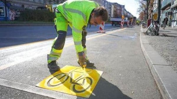 Employee Alexander of the Zeppelin company marks a temporary cycle lane on the Kottbusser Damm in Berlin, Germany, Wednesday, April 22, 2020. Due to the corona pandemic, the establishment of this bicycle lane was accelerated in order to give citizens an incentive to switch to the bicycle. The final installation of a cycle lane on Kottbusser Damm is planned for September 2020. (Joerg Carstensen/dpa via AP) (AP)