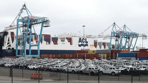 In this file photo taken on March 13, 2019, new Land Rover and Range Rover vehicles are parked on the quayside as cranes stand above a freight container ship at Seaforth Docks, at the Port of Liverpool in Liverpool. (AFP)