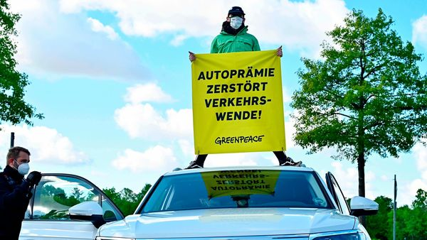 Police officers surrounds a car with a Greenpeace activist on the roof displaying a banner saying
