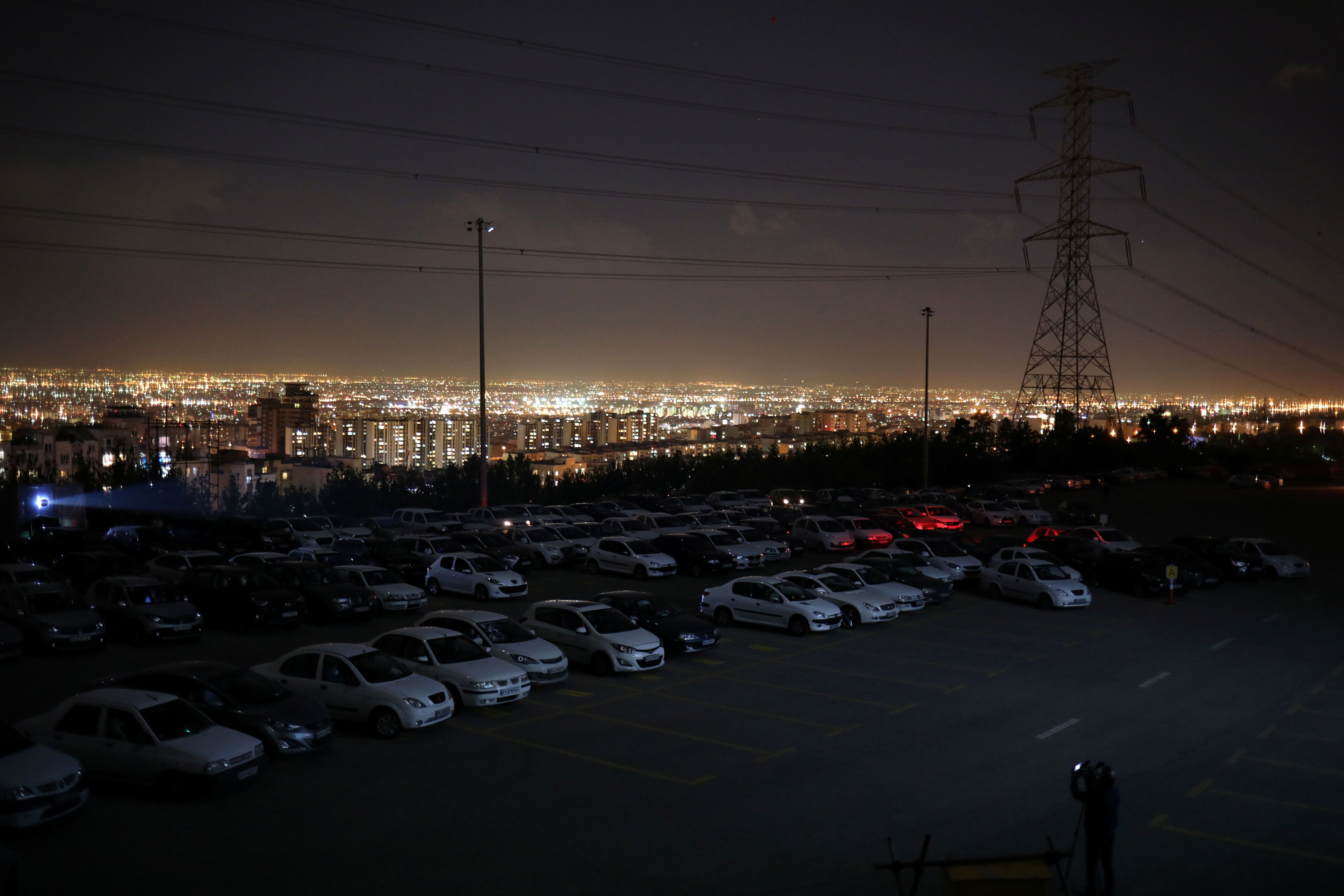 With stadiums shut and movie theaters closed, a drive-in theater now operates from a parking lot right under Tehran's iconic Milad tower, showing a film in line with the views of hard-liners.