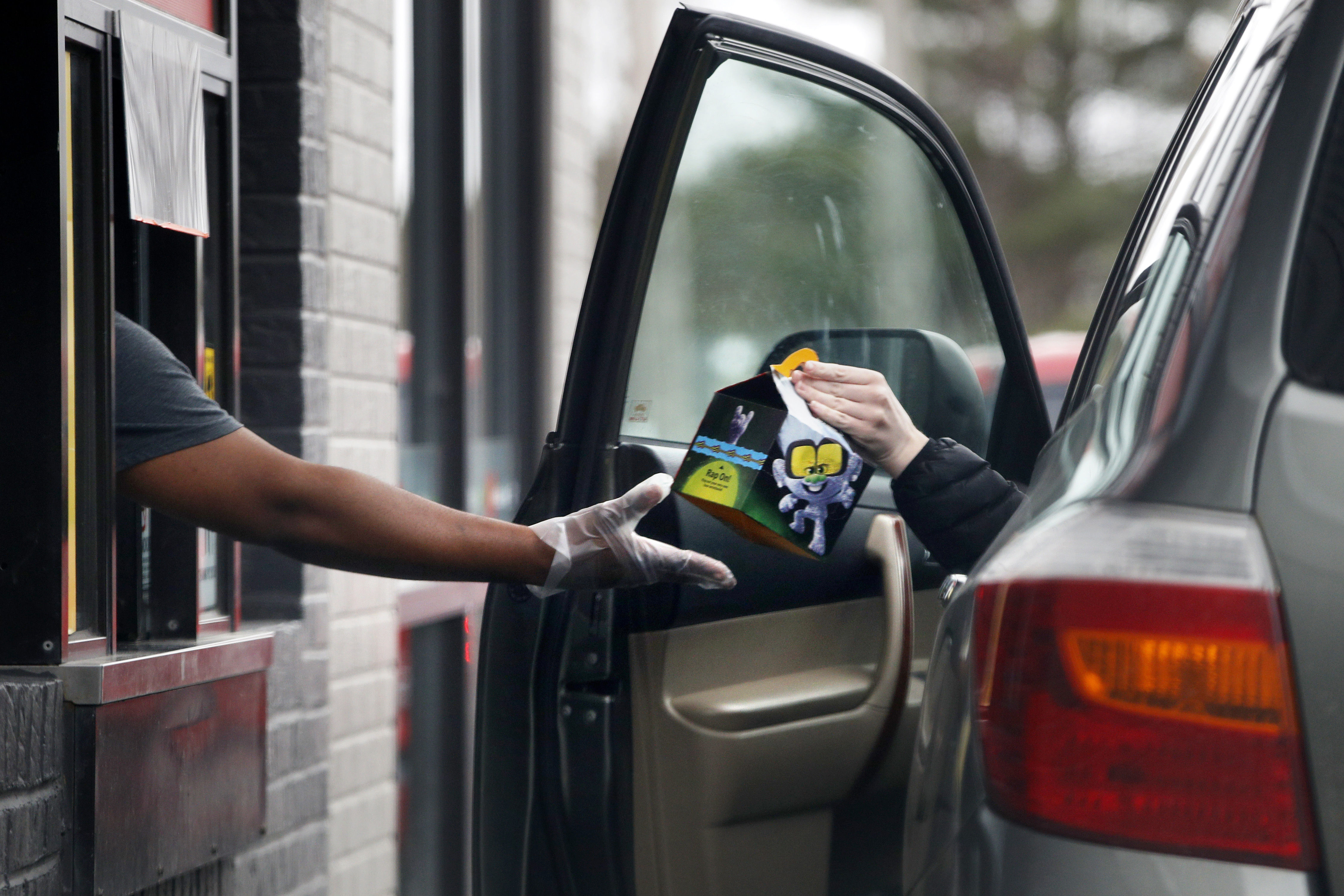 A worker at McDonalds hands a customer a Happy Meal at a drive-through in Augusta,