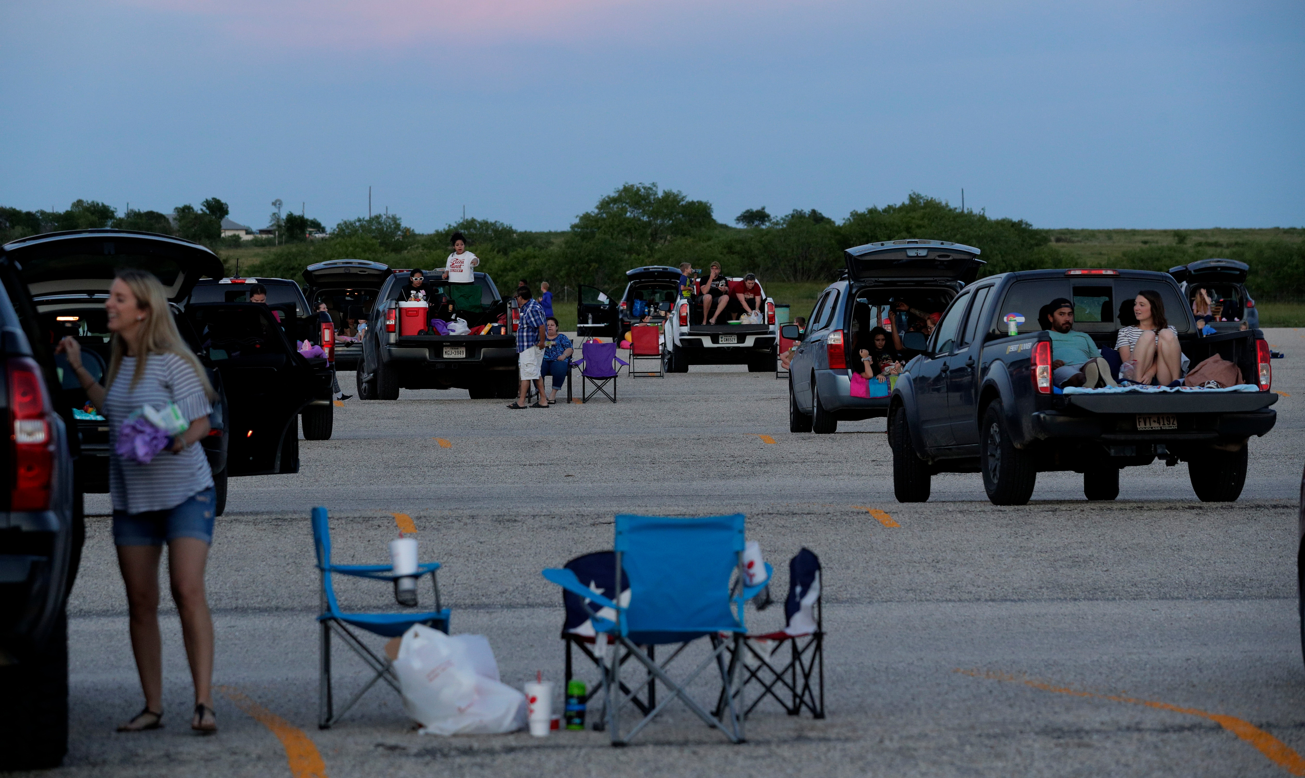 Using social distancing practices, moviegoers arrive at the Stars and Stripes Drive-In Theater in Texas. Families turn the luggage compartment of their cars into a comfortable sitting area while waiting for the movie to start.