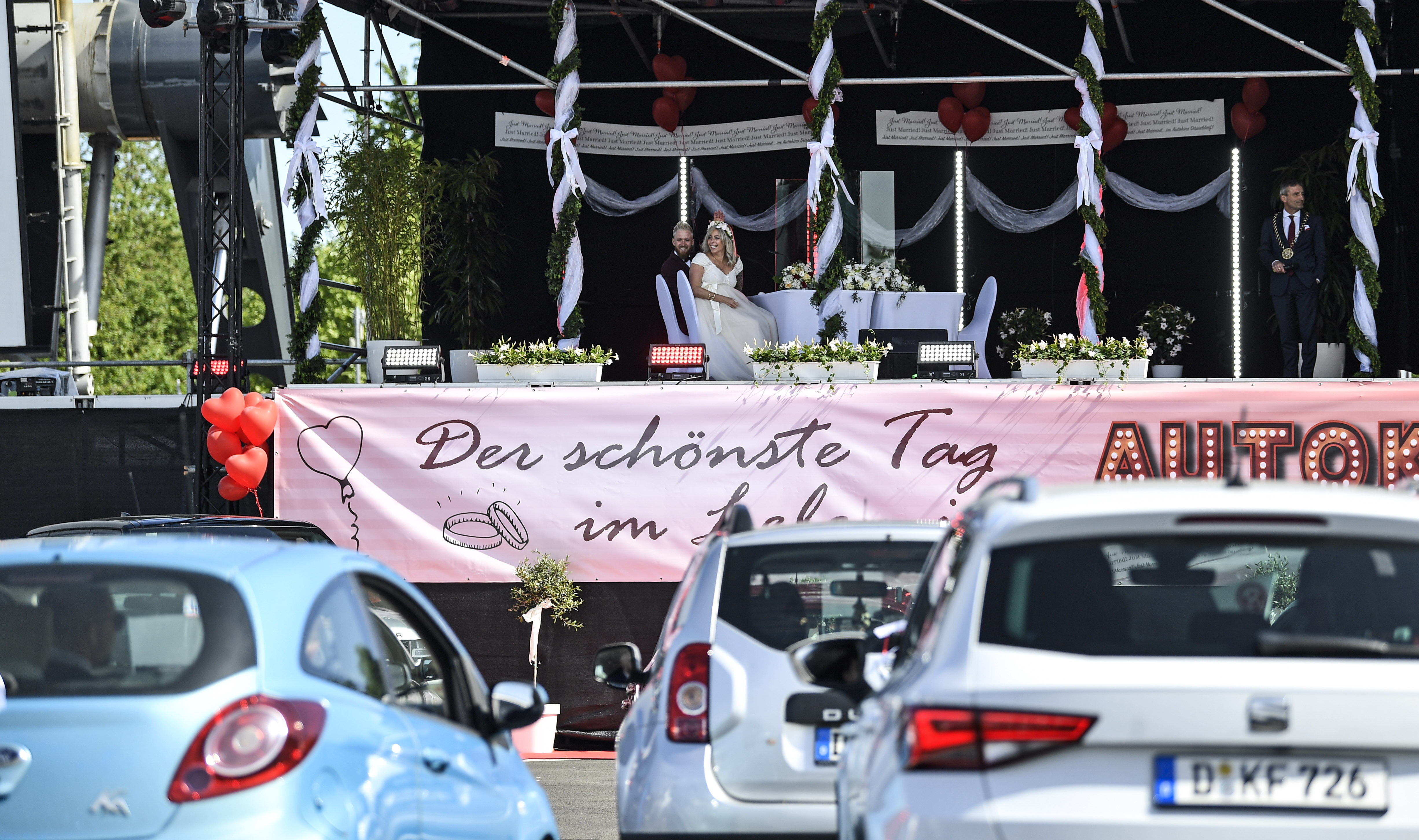 As weddings at registry offices are limited due to coronavirus, a drive-in cinema in Germany has started registering official marriages on its stage. In this picture, relatives and friends of bridal couple - Janine and Philip - attend the marriage ceremonies in their cars.